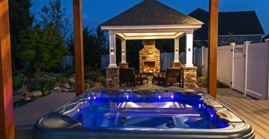 Spa and Outdoor Fireplace: A portable spa set under a pergola — and next to an outdoor pavilion — is the perfect night-time setting.