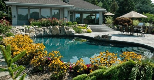 """Backyard Refuge: By expanding the upper patio, we increased the shade area where those leaving the spa or pool can escape the sun. We also refinished the inside of the pool and spa, changing them from white to gray. The new color reacts with the water to give the more desirable 'natural lagoon"""" affect."""