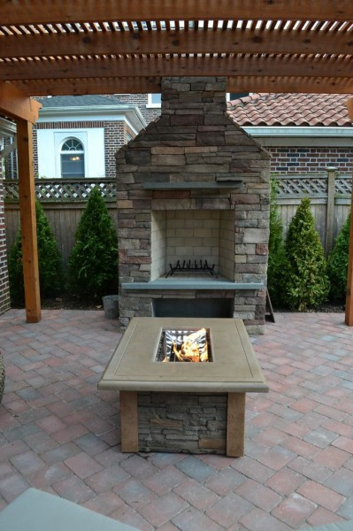 "Outdoor Wood-burning Fireplace: This new wood-burning fireplace is made in cultured stone: Country Ledgestone, in the color ""Bucks County."" The fire pit table is ""Snowbird"" made with a stainless steel burner; its clear fire jewels appear to be bubbling when the flame is lit."