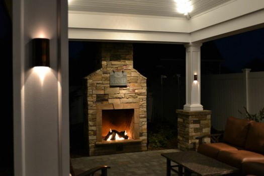 Custom Outdoor Fireplace: Along with this dramatic custom stone-veneered fireplace, the clients also wanted a custom pergola, which is graced with stately white columns on bases veneered in matching stone.