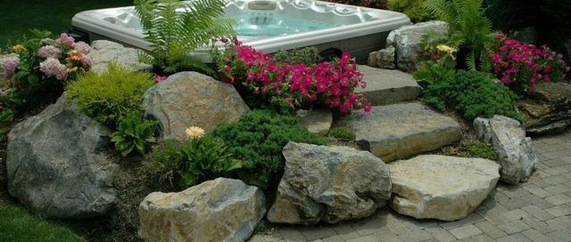 """There are ways to set a spa above ground and it will still appear recessed. For this project (below), we created a secluded area for the hot tub by artfully placing boulders, soil and plants to create a """"spa set in a garden"""" effect. It offers the feel of being in-ground without actually being so."""
