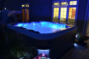 Caption: Exterior LED sconce lights around the outside of a spa perimeter, like this Best Hot Tubs clients', enhance the nighttime allure of your backyard and help create a safe, illuminated spa environment that will tempt you to a pre-nighty-night soak.