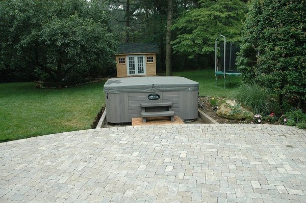 Hot Tub Deliveries: First the delivery. The client's new hot tub was installed at the edge of their patio before customizing the installation began. Note, there is an existing attractive flower bed just to the right making this a great place to position it.