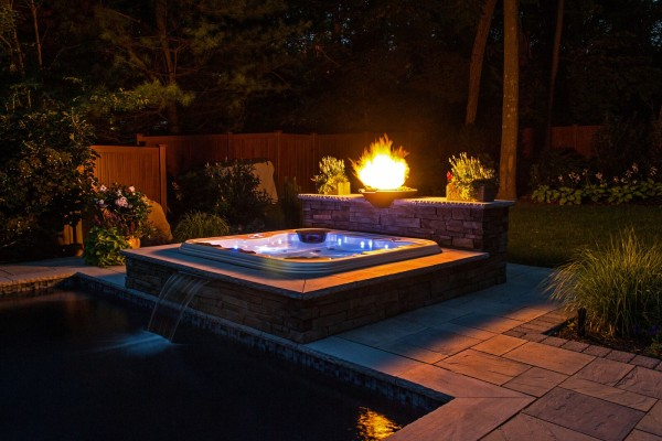 Hot Tub Custom Installation: There are a variety of ways to customize a hot tub water feature beyond leaving it free-standing. It can be recessed into the surface of a beautiful surround, or into a deck or patio. Add a blazing fire pit or bowl and you've got a retreat that you will enjoy often, especially at night.